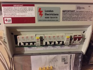 A picture showing a new electrical installation of a Consumer Unit by London Electricians, with a warning sign saying that it needs frequent electrical testing