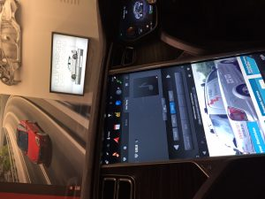 A picture taken inside a Tesla, showing a screen with a photo of the London Electricians van
