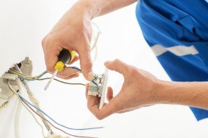 An image of an emergency electrician carrying out work on a plug socket and wiring in a London home