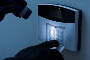 Picture of someone looking at the keypad of a burglar alarm with a torch, wearing black gloves