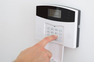 An image of an alarm system, with someone setting the system up by entering a key code