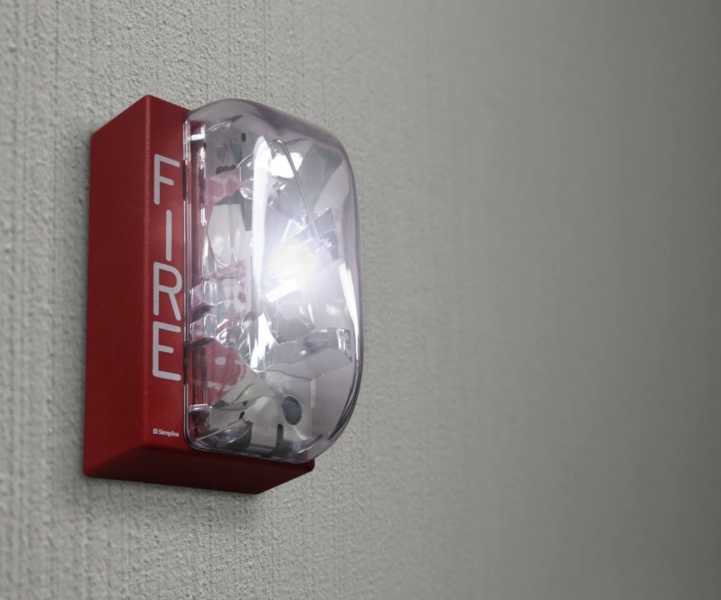 An image of a red fire alarm installed on the wall of a house