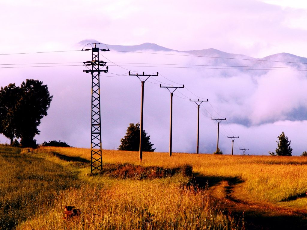 A picture showing electrical pylons spreading out across an open field, a reminder of the need for safely grounding electricity
