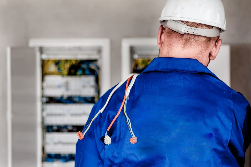 A picture showing a man in a blue shirt and hard hat, part of a blog post on choosing your electrician