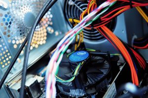 A picture showing wires and a fan inside of a computer, parts of equipment that are checked in electrical testing