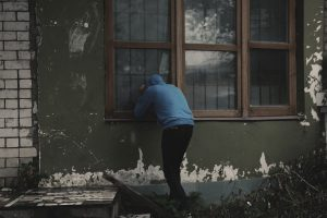 A picture of burglar looking into a house without an intruder alarm or home security
