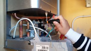A picture of a man fixing electric boiler problems
