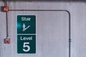 """An image of a fire alarm system installed on a wall, next to a """"stairs"""" sign"""