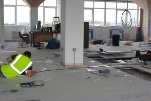 An image of electricians working on the wiring in a commercial property's floors