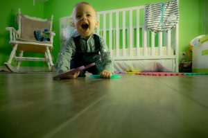 A picture of a toddler in his playroom, one of the places that you should remember when baby proofing your home against the risk of electric shock