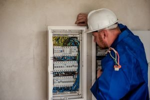 Picture of a qualified electrician working precisely with an electricity board