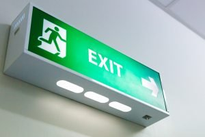 A close-up of an exit sign, an example of emergency lighting in buildings