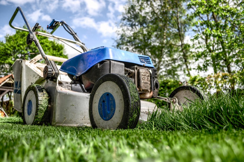 An image showing a lawnmower cutting grass