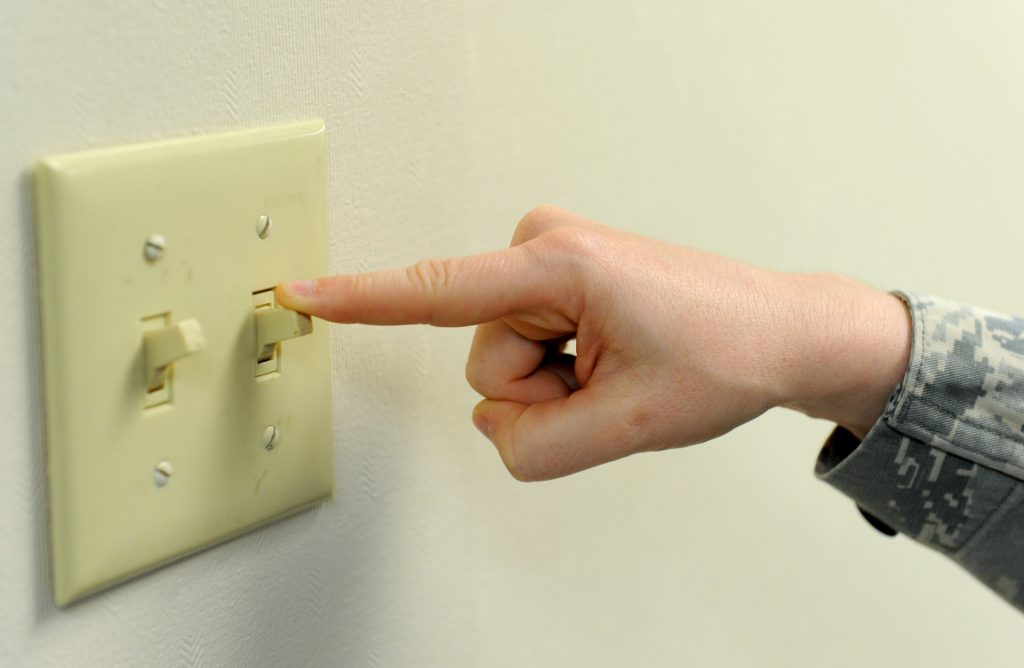 An image of someone carrying out electrical checks by flicking a light switch