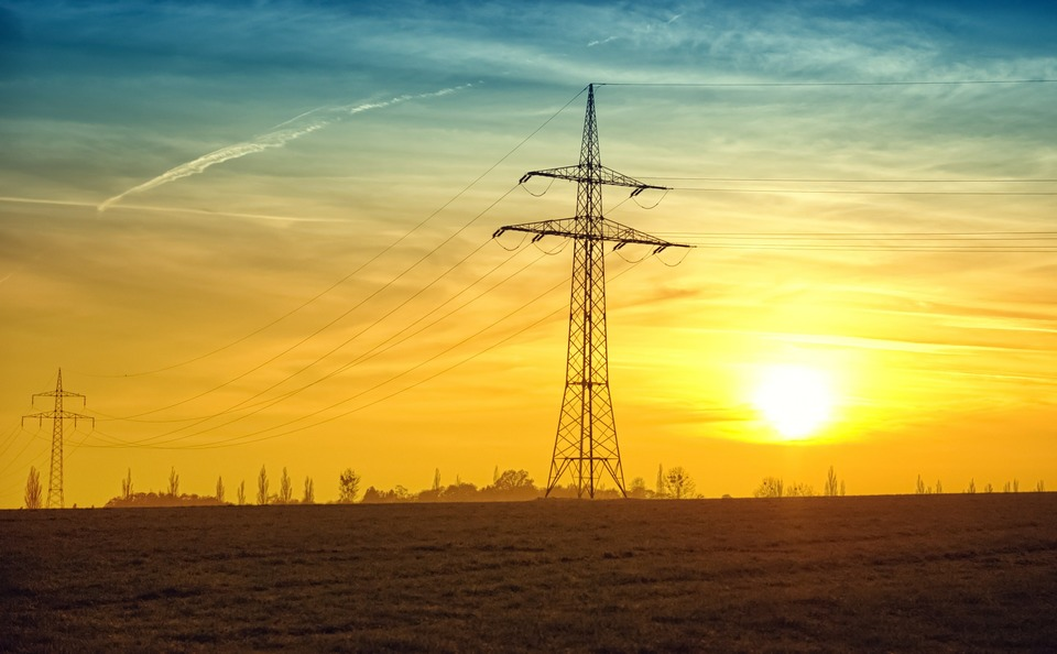 An image of a large electricity transmission tower with the sun setting behind it.