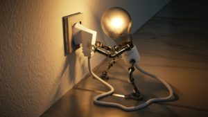 An image of a plug socket, providing electricity to a light bulb.